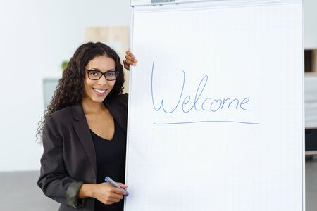 addresses: Smiling confident young businesswoman beginning a presentation with a welcome sign on a flip chart as she addresses a meeting or conference