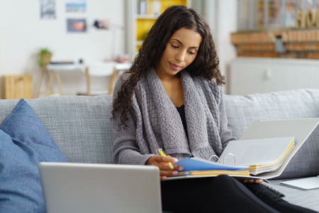 laptop home: African American woman sitting on the sofa while studying hard and taking notes from the books, with bookshelves in the background Stock Photo