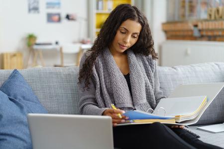 Femme afro-américaine assis sur le canapé tout en étudiant dur et prendre des notes dans les livres, avec des étagères en arrière-plan