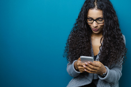 mobile business: Young African American woman reading her mobile phone text messages with a smile, upper body on blue with copy space