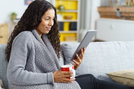 woman reading on tablet at home with a cup of coffee in her hand