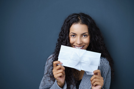 exultant: excited woman holding a envelope with bow and ribbon in her hand standing against dark grey background in studio Stock Photo