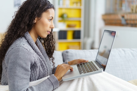 woman snuggling into a white blanket while working on her laptop at home on sofa Standard-Bild