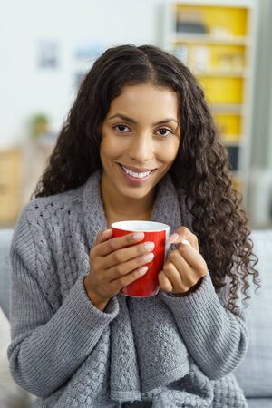 energising: smiling woman sitting at home on her sofa, warming her fingers on a red mug Stock Photo