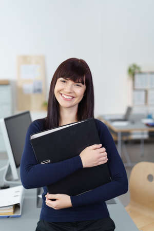 warmly: Charming welcoming businesswoman standing in the office clutching a large binder smiling warmly at the camera