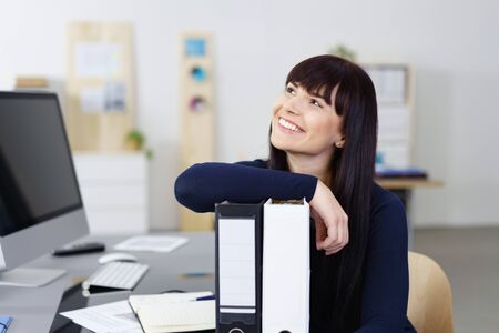 Happy contented young businesswoman sitting at her desk in the office leaning on two large binders smiling with pleasure as she looks into the air with a dreamy expression