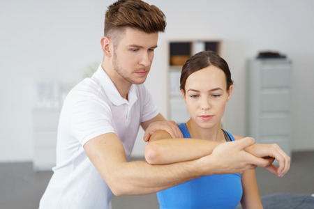 Young Professional Male Physical Therapist Examining the Arm of a Female Patient Inside the Clinic. Banco de Imagens
