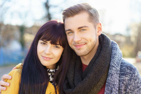 contented: Loving attractive young man and woman standing arm in arm outdoors looking at the camera with happy contented smiles Stock Photo