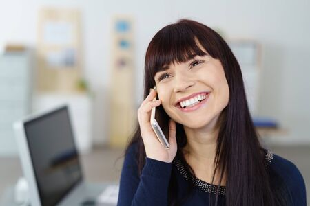 phone conversation: Happy attractive young businesswoman taking a phone call on her mobile grinning with pleasure as she listens to the conversation while standing alongside her desk in the office Stock Photo