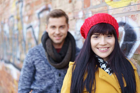 autumn young: cute woman wearing a red cap standing outdoors with her boyfriend in background