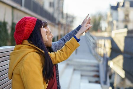 point of view: couple making a sightseeing tour in a city pointing on something above Stock Photo