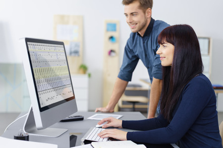successful woman: Two successful hardworking young business colleagues checking a spreadsheet together on a desktop monitor with pleased smiles, man and woman