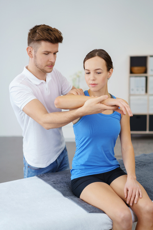 Young Professional Male Physical Therapist Examining the Injured Shoulder of a Female Patient Inside the Clinic.