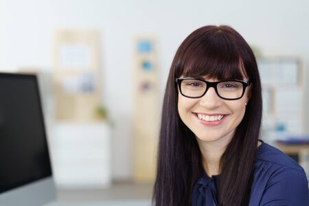 beaming: Smiling businesswoman with a beaming confident smile of welcome sitting at her desk in the office, close sup head shot Stock Photo