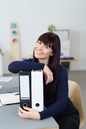 head tilted: Pretty young businesswoman with a charismatic smile leaning on office binders on her desk with her head tilted to the side and a look of pleasure Stock Photo