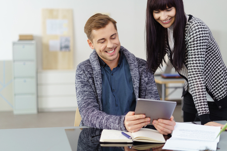 excited woman: Two happy young co-workers in the office smiling as they share information on a tablet computer, man and woman