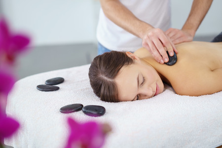 commencing: Young woman enjoying a hot rock massage in a spa salon as heated basalt stones are placed on her muscles prior to commencing the massage
