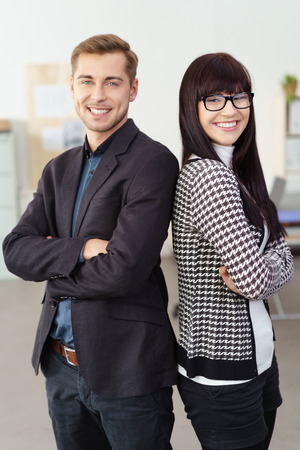 advisers: man and woman standing shoulder on shoulder in the office smiling at the camera with arms folded Stock Photo
