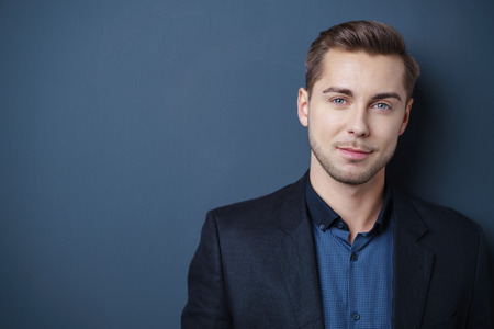 confident young man standing against gray background in studio