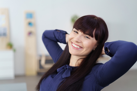 enthusiastic: Smiling relaxed confident young businesswoman leaning back in her chair with her hands clasped behind her head grinning at the camera