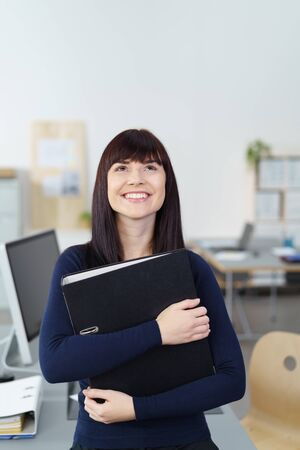 clasping: Attractive happy young businesswoman daydreaming standing in the office clasping a binder and looking up into the air with a smile Stock Photo