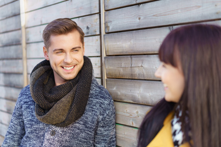 Handsome young man flirting with his girlfriend leaning against a wooden wall grinning happily as he chats to her