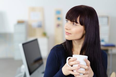 energising: Thoughtful attractive young businesswoman relaxing with a mug of hot coffee at her desk staring pensively off to the side with a serious expression