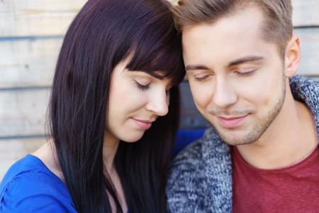 parejas amor: Pareja joven profundamente en el amor de pie muy juntos con sus frentes de tocar y los ojos cerrados disfrutando de un momento de licitación