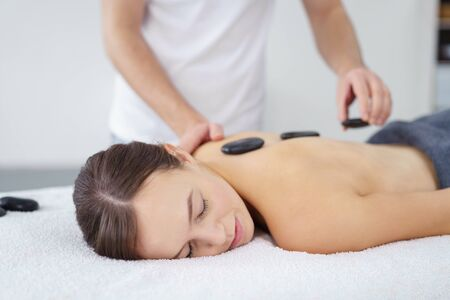 destress: Young woman having a hot stone massage at a spa to de-stress and relax her muscles as hot basalt stones are place along her spine by the therapist Stock Photo