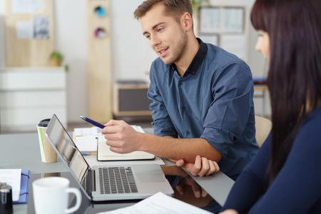 empleados trabajando: Joven hombre de negocios en una reunión con una atractiva colega femenina discutir la información en un ordenador portátil en un concepto de trabajo en equipo Foto de archivo