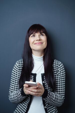 young woman smiling: Waist Up Portrait of Cheerful Smiling Young Woman with Dark Hair Wearing Black and White Patterned Jacket Looking Up While Holding Cell Phone in Studio with Navy Blue Background Stock Photo