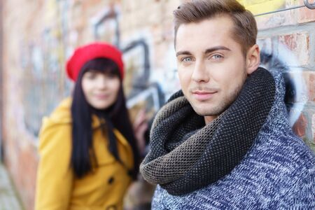 waist up: waist up portrait of a fashionable young couple standing outside in autumn or winter