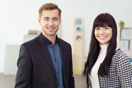 ambitious: Successful ambitious young business team with an attractive friendly man and woman posing together in the office