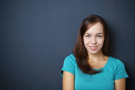 appealing attractive: Pretty Young Woman Smiling at the Camera Against Dark Gray Wall with Copy Space on the Left Side.