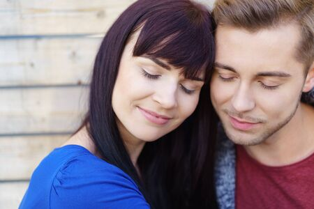 Young couple deeply in love sharing a tender moment cuddling together outdoors with their eyes closed in bliss and pleasure, close up view Stock Photo