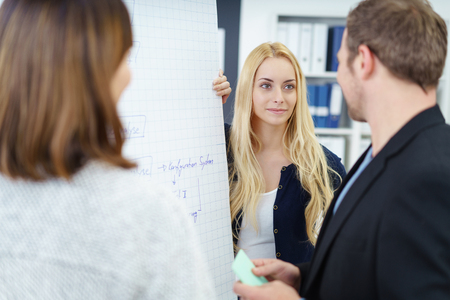 flip chart: Business team working together on a project standing grouped together in front of a flip chart with focus to a serious pretty young blond businesswoman