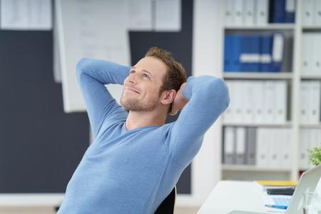 Relajado hombre de negocios exitoso sentado soñando en su silla en la oficina con las manos entrelazadas detrás de la cabeza y una sonrisa de satisfacción Foto de archivo