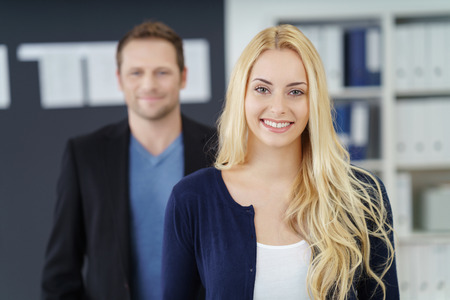 co operation: Confident young female manageress or business team leader standing smiling at the camera with a male colleague in the background