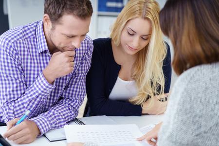 書類を説明するプレゼンテーションを机の上に傾き、彼女の事務所で若いカップルにブローカー
