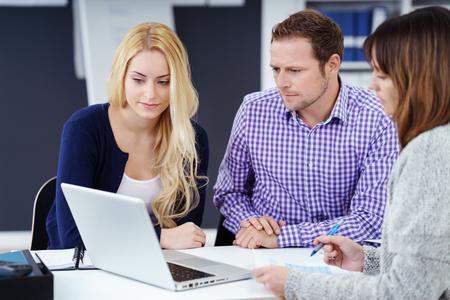 Tres compañeros de trabajo en una reunión sentado agrupan en torno a una lectura de información ordenador portátil en la pantalla