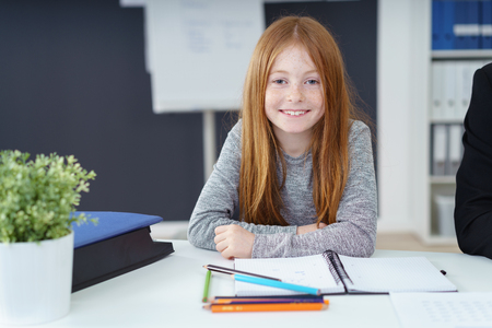 Cute little redhead girl with a lovely engaging smile sitting at a desk in an office doing her homework