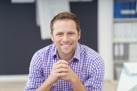 잘 생긴 젊은 사업가 카메라, 비공식적 인 체크 보라색 셔츠를 직접보고 사무실에 앉아 행복 미소로 스톡 콘텐츠