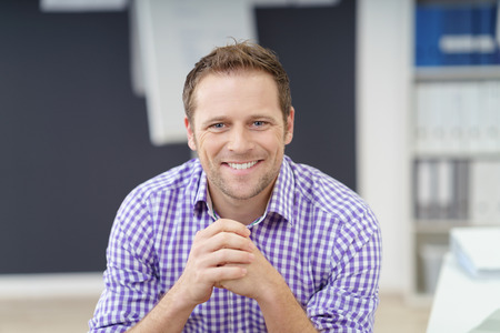 looking to camera: Handsome young businessman with a happy smile sitting in the office looking directly at the camera, informal checked purple shirt