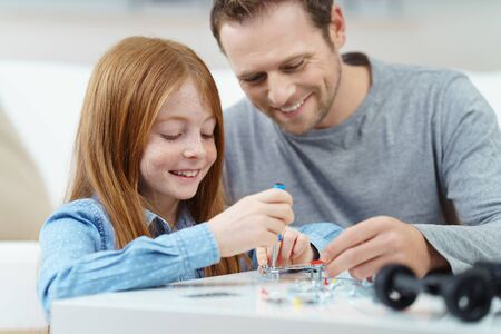 small table: Father and daughter working on a project together using a screwdriver as he shows her how to assemble objects, both smiling happily with focus to the child Stock Photo