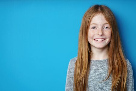engaging: Pretty young redhead girl with an engaging smile standing in front of turquoise blue background with copy space