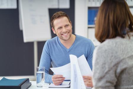 Atractivo joven hombre de negocios informal con una sonrisa amistosa discutiendo el papeleo con una compañera de trabajo en la oficina