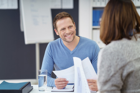 paperwork: Attractive informal young businessman with a friendly smile discussing paperwork with a female colleague in the office Stock Photo