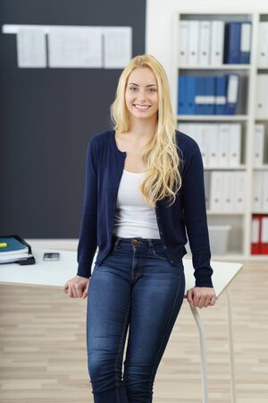 casual office: Relaxed confident young businesswoman in jeans standing perched on the edge of an office table beaming happily at the camera Stock Photo