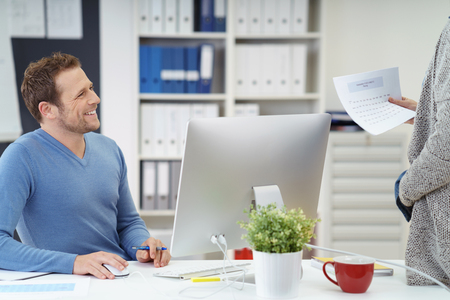 co operation: Smiling friendly businessman talking to a co-worker or his secretary who is holding a document as he sits at his desk in the office behind a desktop computer Stock Photo