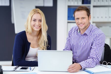 co operation: Successful young business team, a man and woman, sitting at a desk in the office working on a laptop computer smiling at the camera Stock Photo